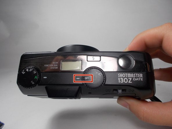 """First, make sure that the camera is turned off. The dial must line up the word """"off"""" with the white tally mark."""