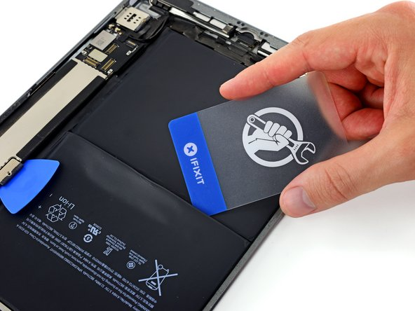 Re-insert a corner of your plastic card under the upper battery cell, near the left edge of the iPad.