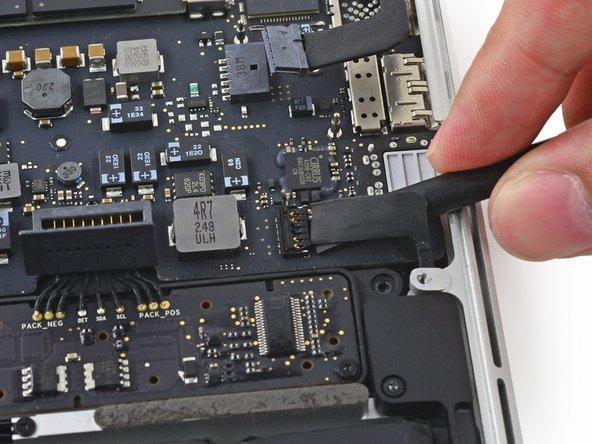 スパッジャーの平面側先端をコネクター付近の左側スピーカーケーブルの下に差し込み、ソケットからまっすぐ持ち上げて作業の邪魔にならないように折り曲げます。