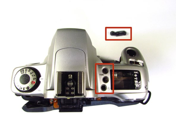 Buttons may slip out of the camera's top as the top is pulled off the camera (shown in picture two).