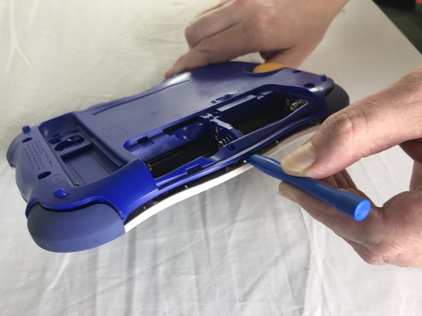 Using the plastic opening tool, detach the back plate from the front piece.