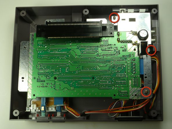 Remove the three 13.25mm Phillips screws that secure the motherboard to the lower case with a Phillips head #2 screwdriver.