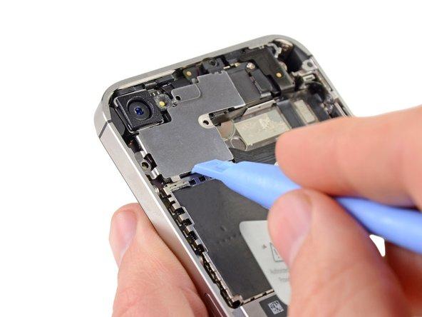 С помощью пластиковой лопатки подденьте экранирующую крышку.