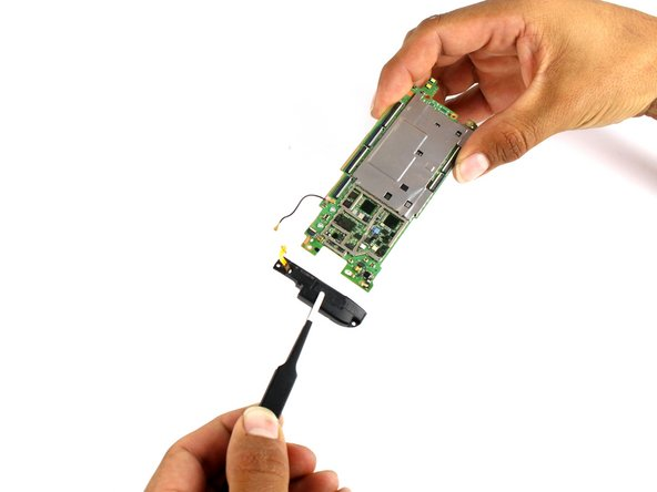 Use a pair of tweezers to gently remove the bottom speaker from the motherboard.