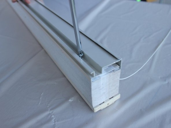 Take out the screw using the phillips screwdriver and slide the top rail off.