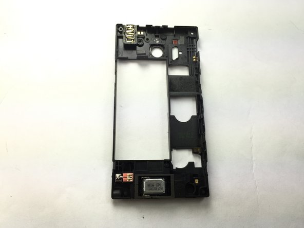 Flip over the black back cover and locate the speaker phone at the bottom, then use the tweezers to remove the speaker. It is glued to the back cover so a little force will be needed.