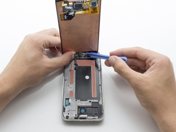 Continue to lift the display. You will notice a black cable connecting the home button to the motherboard.