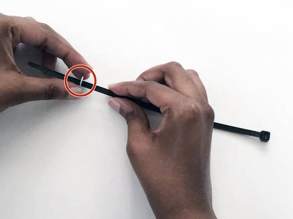Pass the metal flat washer through the second 8-inch zip tie.