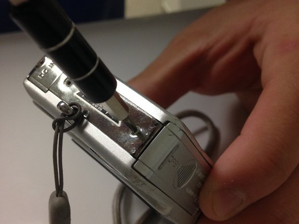 Remove the top screw with the screwdriver.