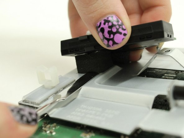 Use a flat prying tool to cut under the foam holding the WiFi module to the motherboard assembly.