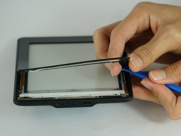 Gently pry the bezel off the screen using a plastic opening tool. Start at the corners and slide around the edges until you return to your starting point.