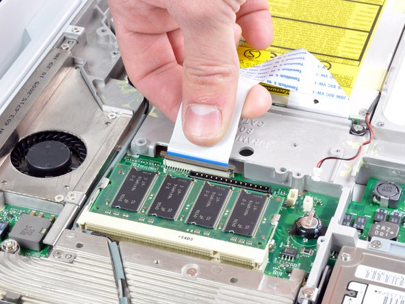 Image 1/1: Release the optical drive ribbon clamp as described above. Slide the optical drive ribbon out of its connector.