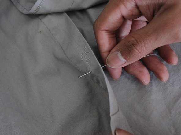 Begin sewing by putting the needle through the back of the fabric, out to the front, and through a hole in the button.