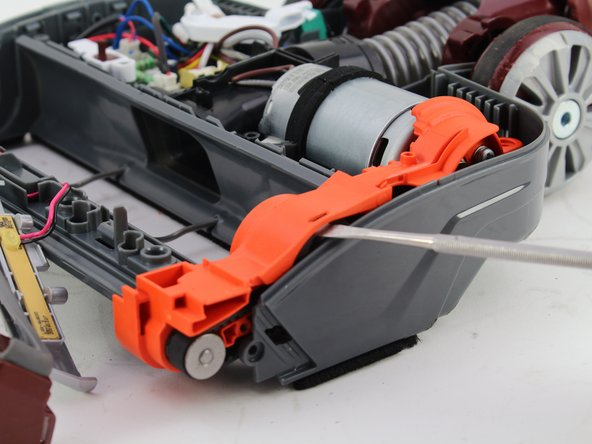 Use the spudger to detach the orange drive belt compartment from the vacuum.