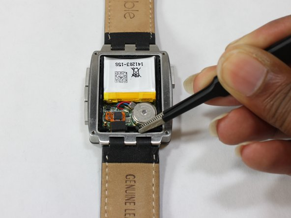 The plastic frame is clipped inside the steel body with four clips, two each on the left and the right side of the watch, near the corners. You can stick a small screwdriver into the cutouts right above the clips and gently lever the plastic frame up, corner by corner.