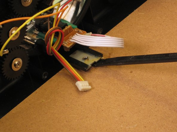 With the flat end of a spudger, scrape away the glue between the mounting tabs and the bottom of the radio.
