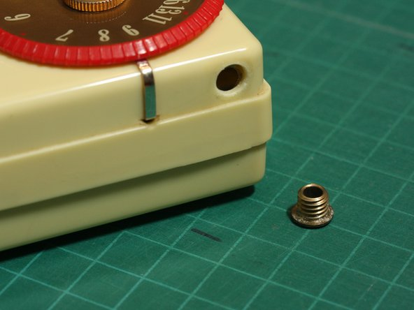 Image 2/2: Unscrew and remove the metal jack collar using a flathead screwdriver or other flat tool.