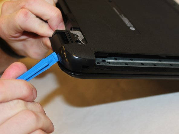 Use the spudger to press the tabs in the back of the computer. Carefully remove the back of the laptop by prying around the sides using the plastic opening tool.