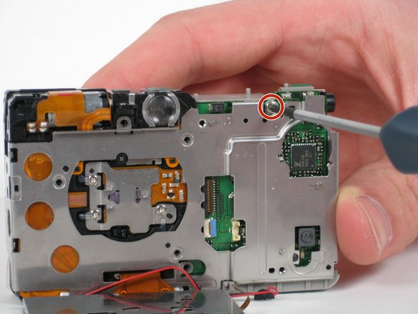 Remove the one 4.3 mm Phillips screw that is now visible, which is located at the top right of the back of the camera.