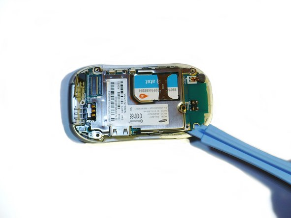 Use the Ipod Opening Tool to lift the green logic board carefully.