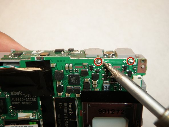 Touch the soldering iron tip to the solder in the upper right corner connecting the logic board to the battery lead.