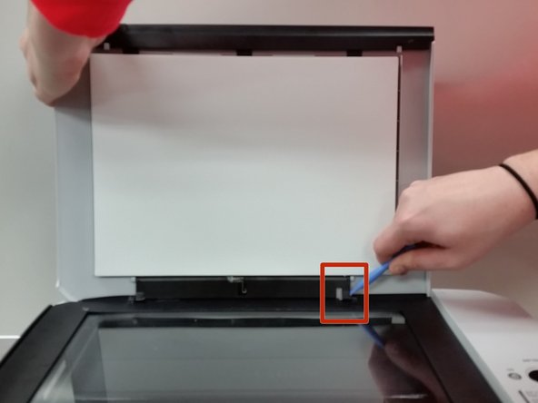 Lift scanning bed cover with one hand, and pry the right hinge inward using a plastic opening tool.