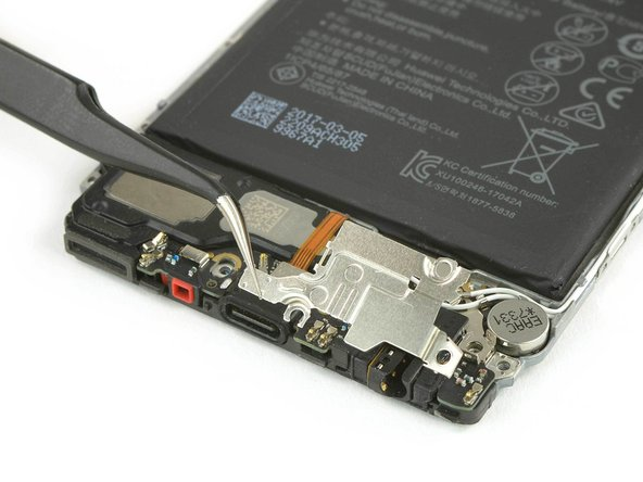 Remove the metal shield covering the charging board with tweezers.