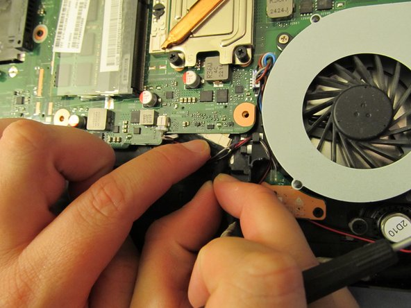 Image 1/1: Carefully tug the LCD cable out from under the motherboard.