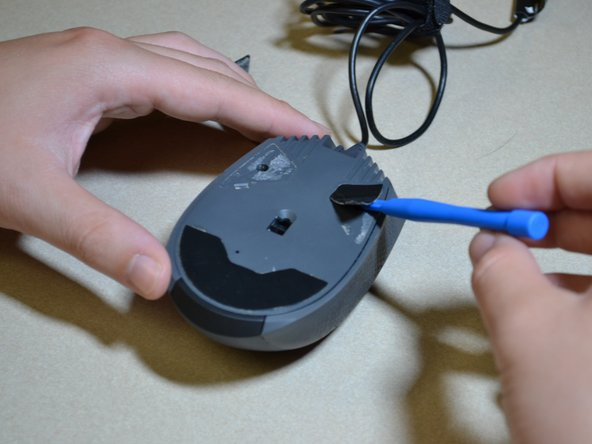 Remove the three skates on the bottom of the mouse using the plastic opening tools.