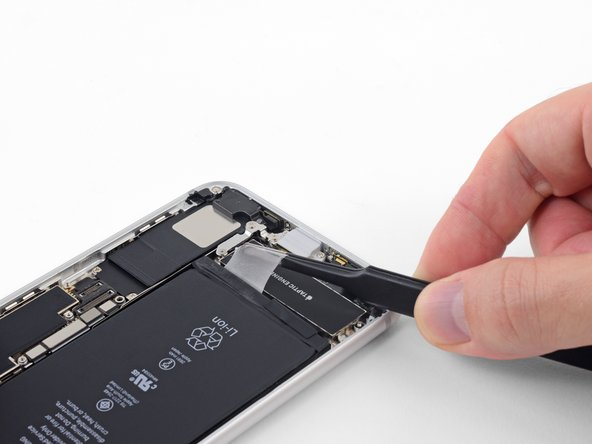 Slowly but steadily, pull the adhesive tab up and away from the battery, toward the bottom edge of the iPhone.