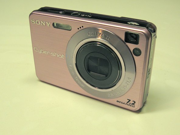 Image 1/3: Turn the camera over and gently push the battery door toward the side.
