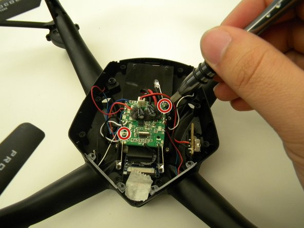 Remove the two (2) 5mm screws attaching the Motherboard to the body of the drone using a JIS #00 screwdriver.