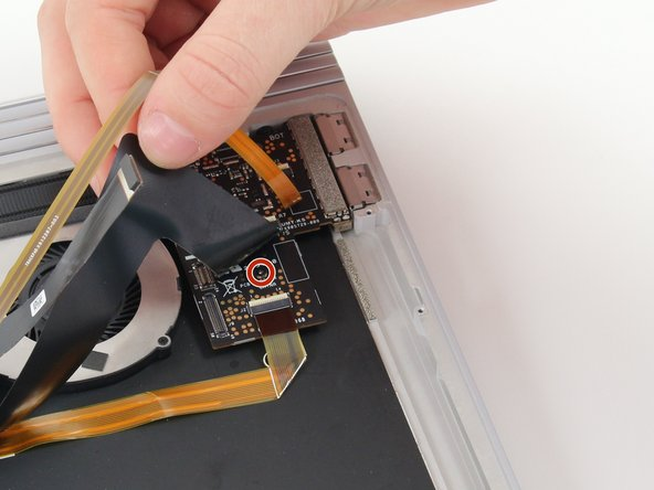 Lift up the black and gold wires and find the screw hidden there.