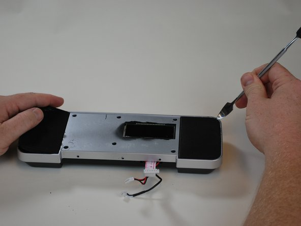 Using the metal spudger, lift the speaker grilles from the display.