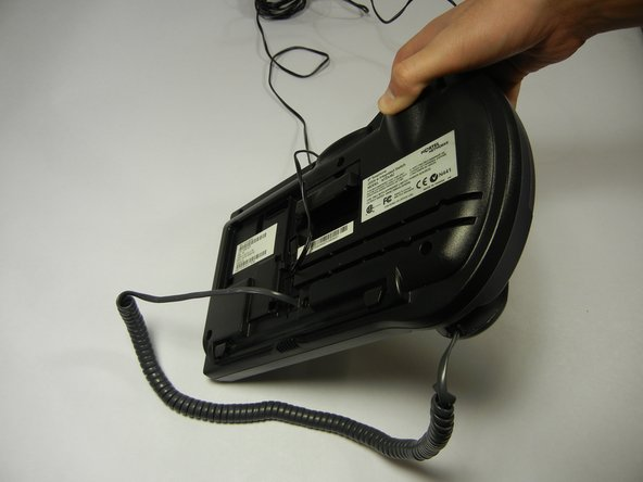 Image 1/2: Disconnect the handset cord from the back of the telephone by squeezing the clip and pulling striaght out.