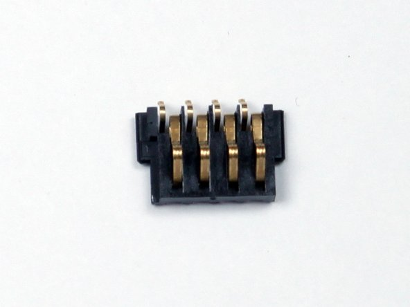 The small plastic piece with four metal pins is the battery terminal shown in the third picture.