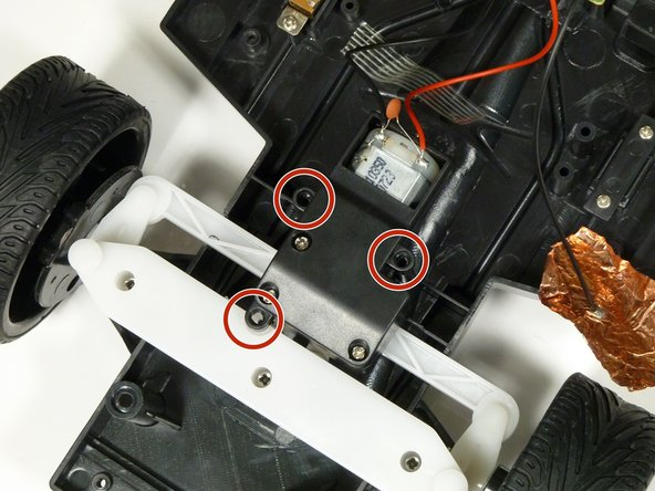 Remove the three 1.6mm Phillips #000 screws from the black motor casing