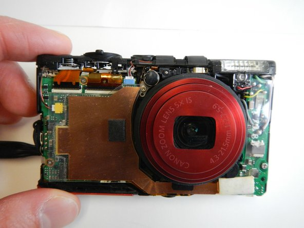 Carefully remove the large copper ribbon on the front of the camera (attached with adhesive pads)