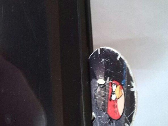 Introducir un objeto plano y plástico para separar la tapa trasera del marco de la pantalla