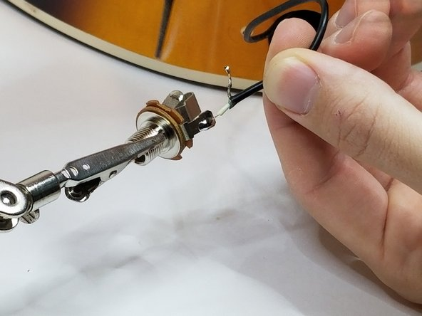 Touch the hot wire to the hot conductor tab and heat with the soldering iron until they melt together.