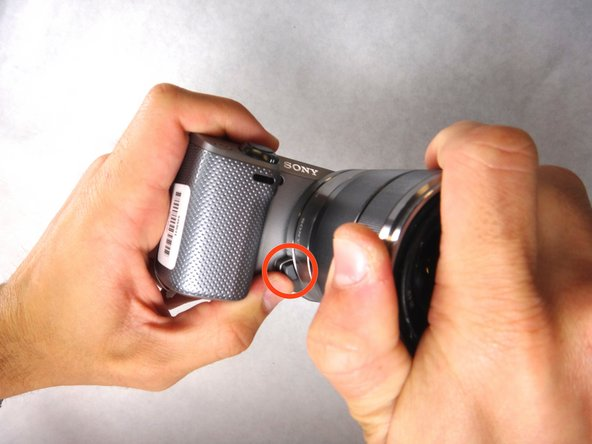 Hold lens and camera securely with two hands.
