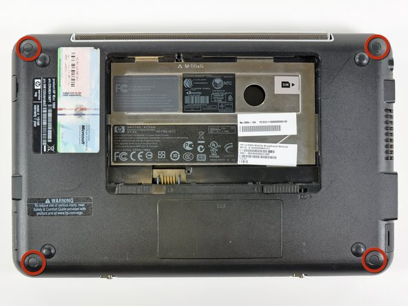 Using the sharp tip of a spudger, pry and remove the four plastic screw covers from the underside of the HP Mini 1000.