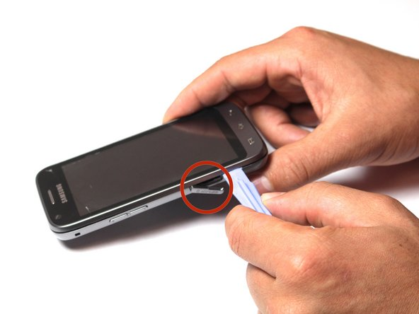 Image 1/1: Insert the tool into the SD card slot and pry around the entire phone.