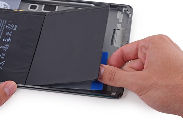 Place the plastic card underneath the lower left corner of the battery.