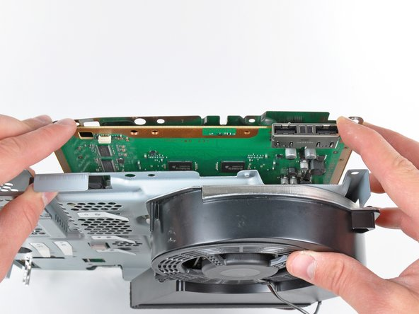Image 1/1: If necessary, gently pry the motherboard off the top shield near the heat sink and its shroud.