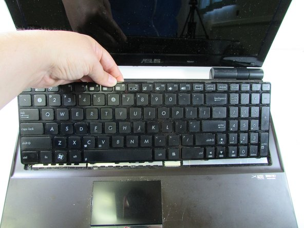 Once the keyboard is free, lift it up slightly and release the cable connection underneath.