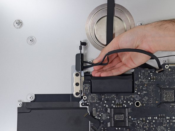 Pull the cable and connector through the right hard drive bracket. Move the cable to the right side of the iMac, out of the way of the exhaust port.