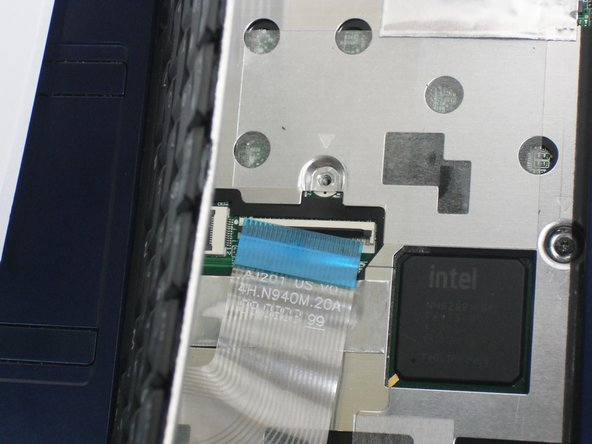 Image 2/2: Disconnect the ribbon by lifting the black plastic hinge and removing the clear blue cable.