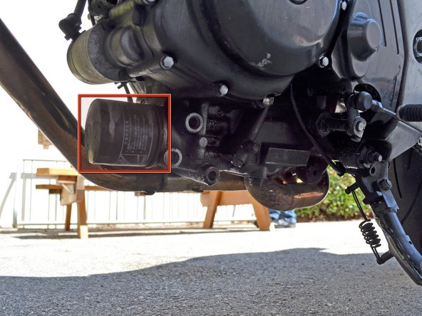 Locate the oil filter under the bike and slide the oil drain pan underneath it to catch draining oil.