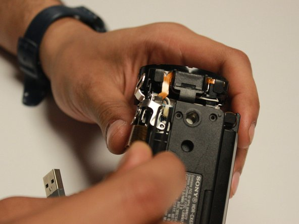Image 1/1: By the metal tweezers, remove the white wire that is connecting the shutter assembly and  motherboard